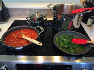 Cooking up pasta sauce and sauteed greens.  Soup is simmering in the pot on the back of the stove.  I'm definitely a multitasker!